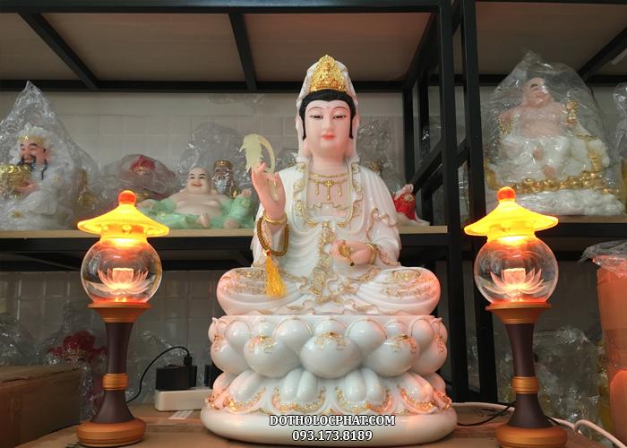 Tượng Mẹ Quán Thế m Bồ tát trắng viền vàng được thể hiện trong tư thế ngồi từ bi trên tòa sen, một tay đeo chuỗi tràng hạt, cầm thùy dương liễu, tay kia cầm bình cam lồ