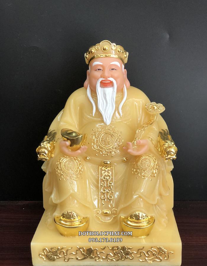 Tượng Thần Tài với y phục trang nghiêm, một tay cầm đĩnh vàng tay kia cầm ngọc như ý