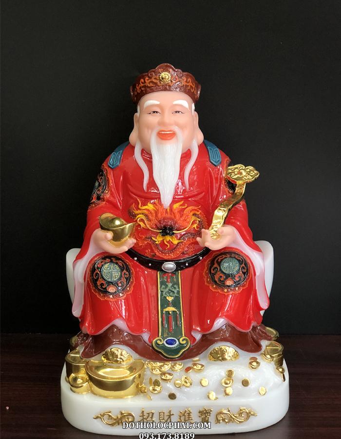 Tượng Thần Tài màu đỏ gấm, được khắc họ với dáng vẻ uy nghiêm tôn quý, tay cầm một thỏi vàng lớn, râu tóc bạc phơ, y phục chỉnh tề
